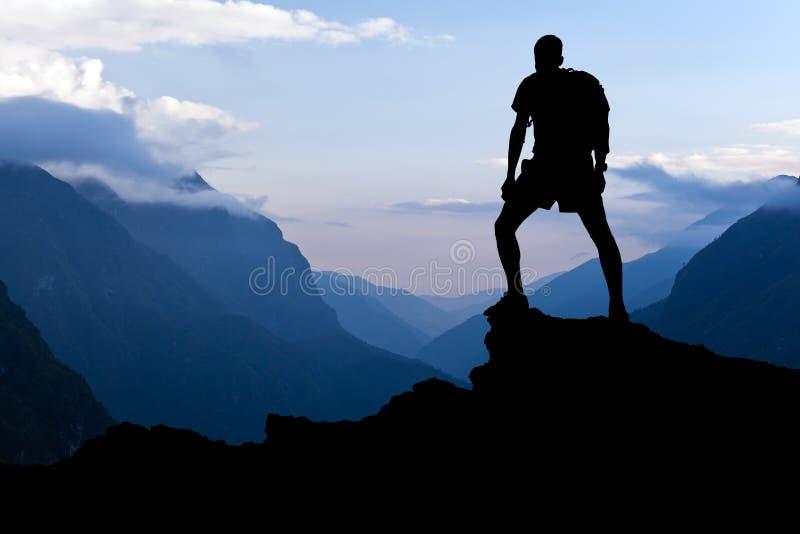 Uomo che fa un'escursione la siluetta di successo in montagne immagine stock