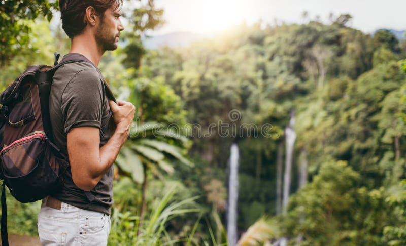 Uomo che fa un'escursione vicino alla cascata fotografia stock libera da diritti