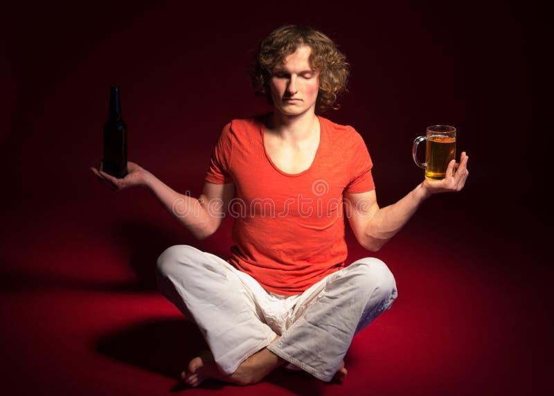 Uomo che fa yoga con birra immagini stock