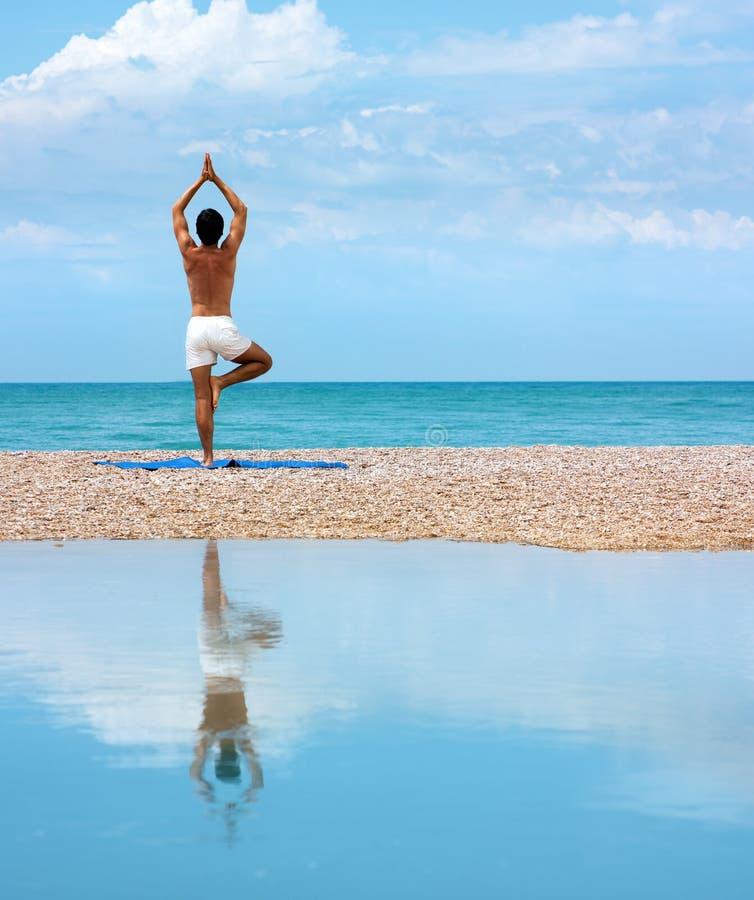 Uomo che fa yoga. Posa di Vrikshasana (l'albero) fotografia stock libera da diritti