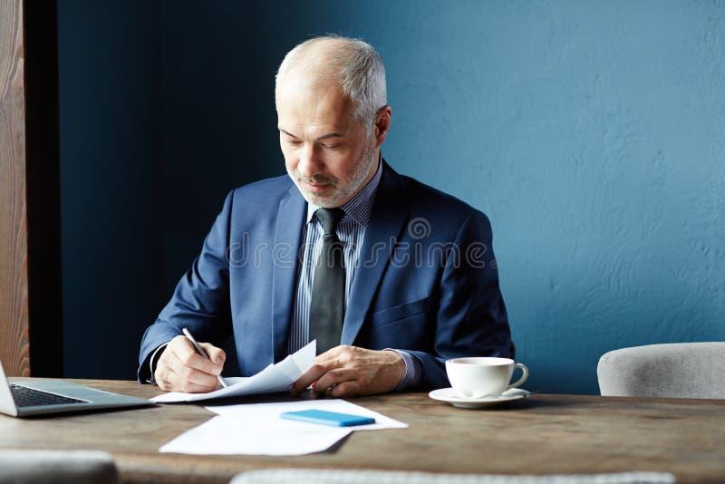 Uomo che firma un contratto fotografia stock libera da diritti