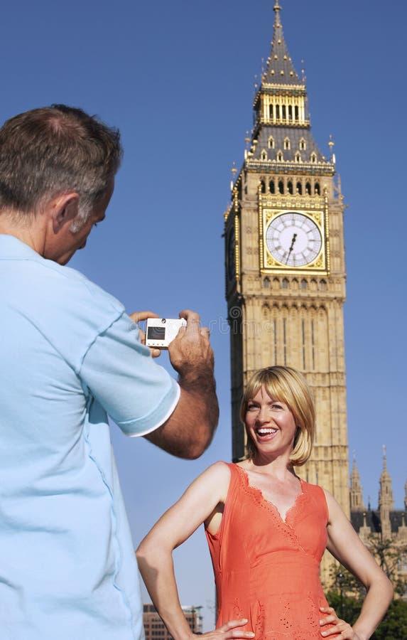 Uomo che fotografa donna contro grande Ben Tower immagine stock libera da diritti