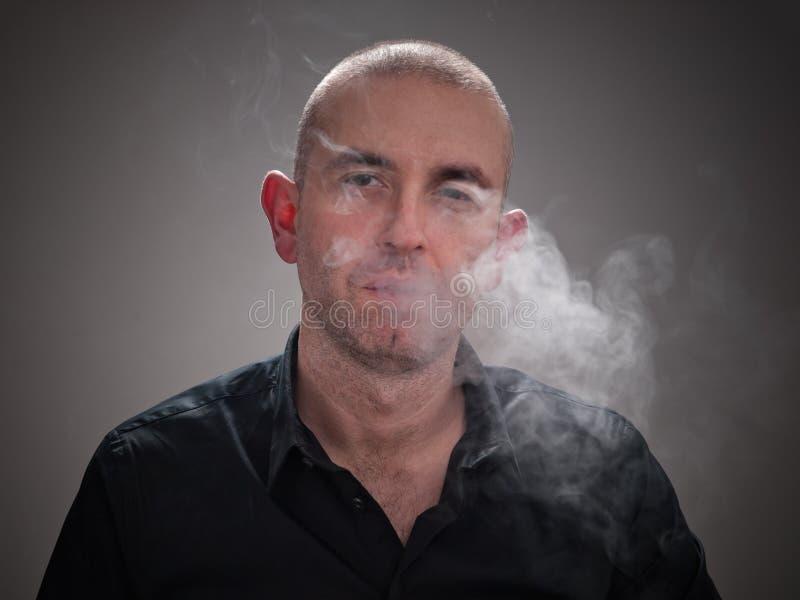 Uomo che fuma con il fumo nel suo fronte immagini stock