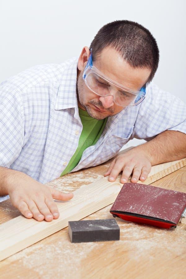 Uomo che furbishing planck di legno immagine stock