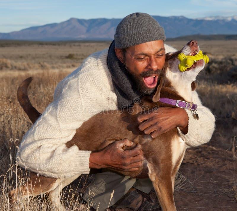 Uomo che gioca con il cane fotografia stock