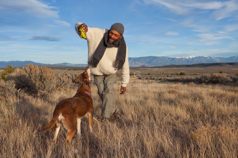 Uomo che gioca con il suo cane fotografia stock