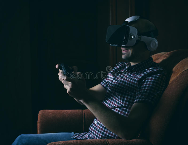 Uomo che gioca i video giochi che indossano gli occhiali di protezione di realtà virtuale immagini stock libere da diritti