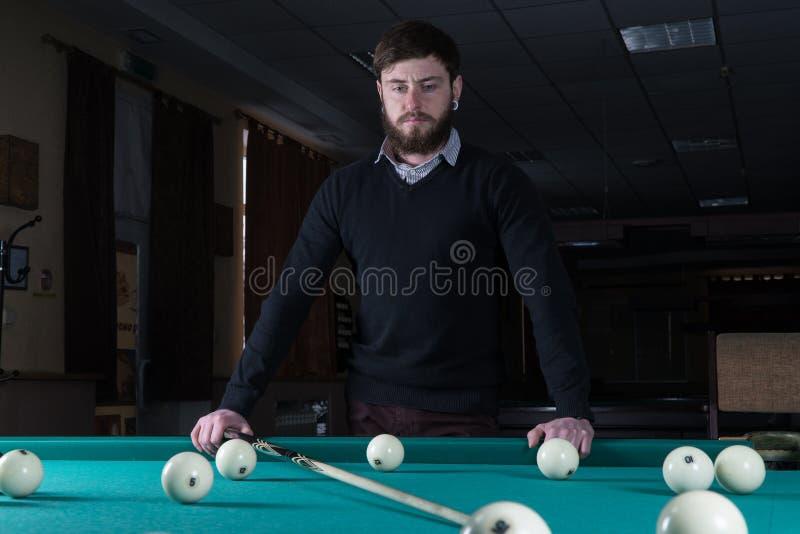 Uomo che gioca il biliardo passi il tempo che gioca il biliardo fotografie stock libere da diritti