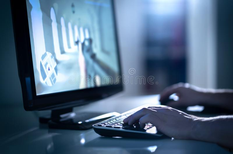 Uomo che gioca il video gioco dei fps con il desktop computer La E mette in mostra professionale nell'evento competitivo fotografia stock libera da diritti