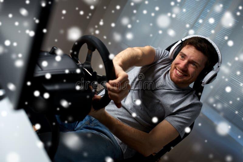 Uomo che gioca il video gioco di corsa di automobile a casa fotografia stock