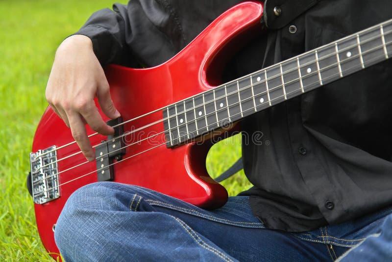 Uomo che gioca la chitarra bassa fotografia stock
