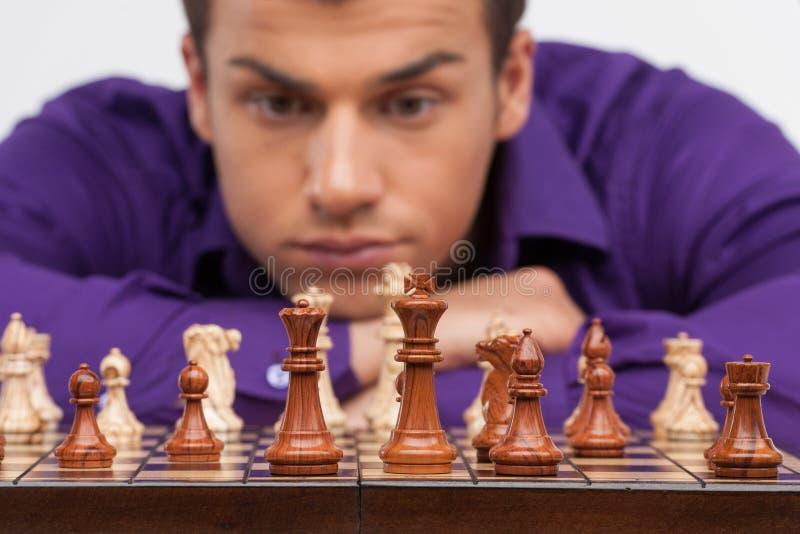 Uomo che gioca scacchi su fondo bianco fotografie stock libere da diritti