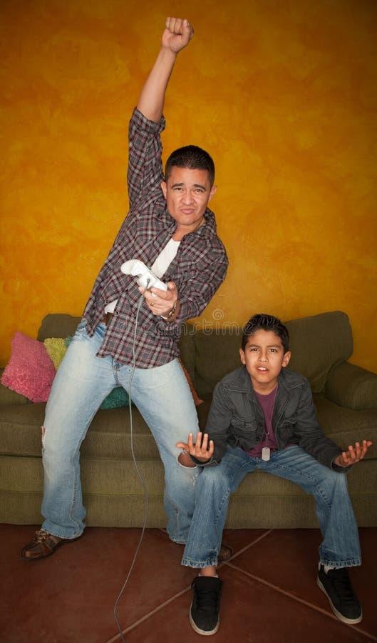 Uomo che gioca video gioco con il giovane ragazzo annoiato fotografia stock