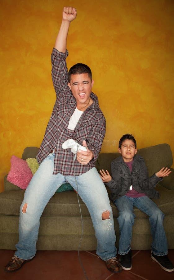 Uomo che gioca video gioco con il giovane ragazzo annoiato fotografie stock libere da diritti