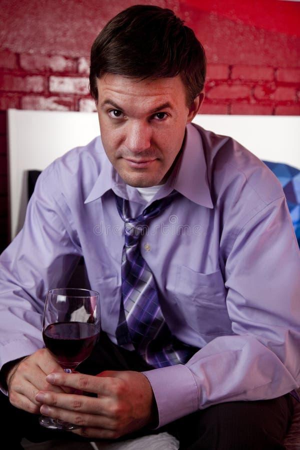 Uomo che gode di un bicchiere di vino a casa fotografia stock
