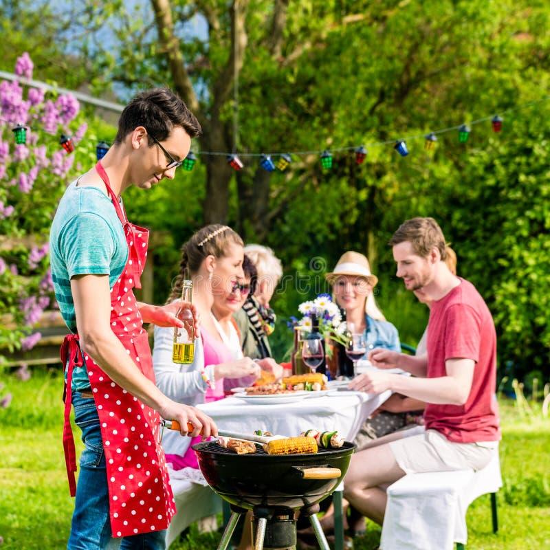 Uomo che griglia carne sul partito del barbecue del giardino immagine stock