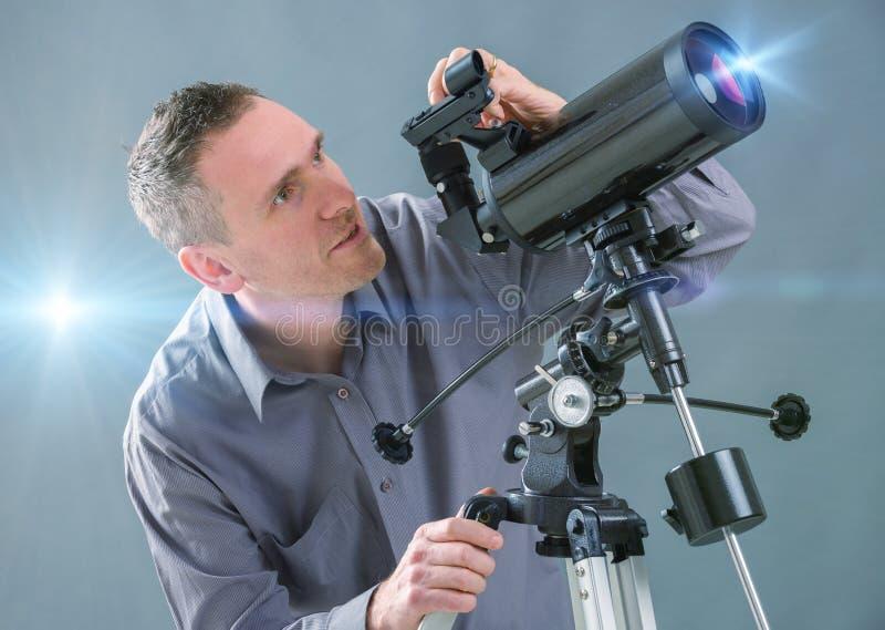 Uomo che guarda tramite il telescopio immagine stock