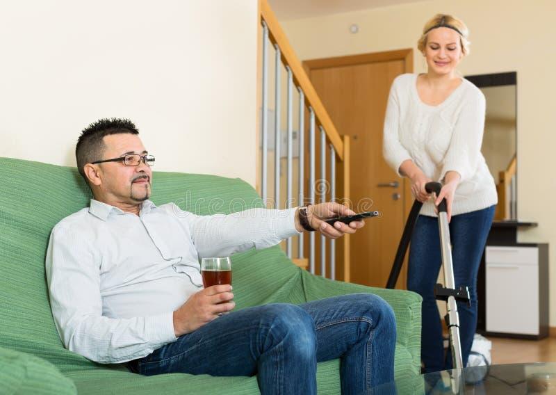 Uomo che guarda TV mentre la donna pulisce immagine stock libera da diritti
