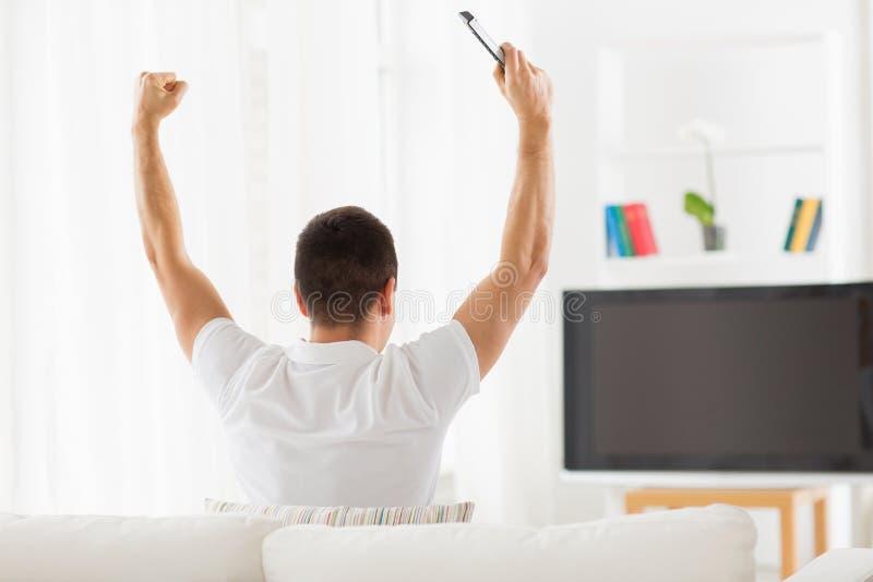 Uomo che guardano TV e gruppo di sostegno a casa fotografia stock libera da diritti
