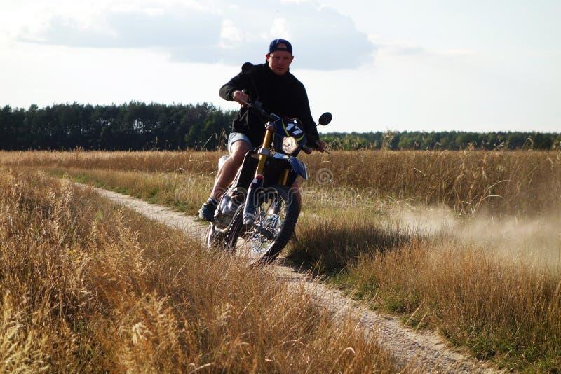 Uomo che guida motocicletta trasversale sulla strada campestre immagini stock libere da diritti