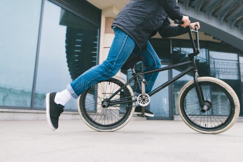 Uomo che guida una bici di BMX nella città sui precedenti di architettura ciclare Cultura di BMX fotografie stock