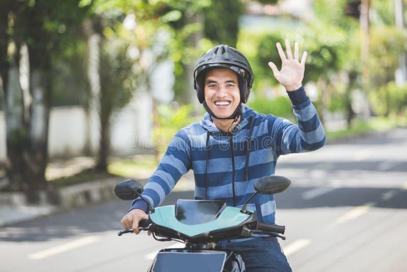 Uomo che guida una motocicletta e che ondeggia mano fotografia stock