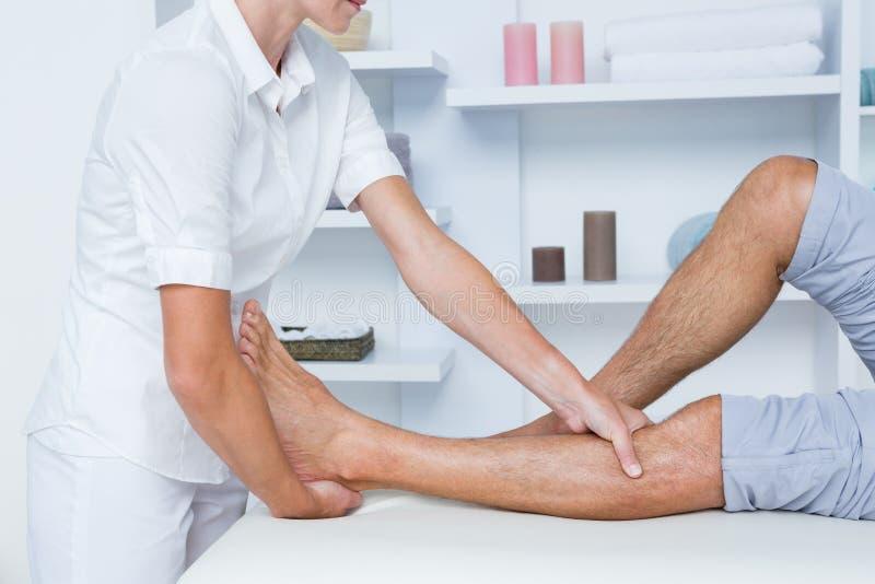 Uomo che ha massaggio della gamba fotografie stock libere da diritti