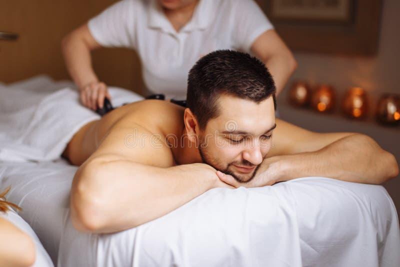 Uomo che ha massaggio di pietra nel salone della stazione termale Concetto sano di stile di vita fotografia stock libera da diritti