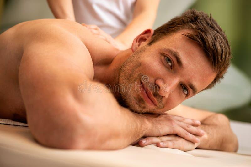 Uomo che ha massaggio posteriore nella stazione termale di salute immagine stock