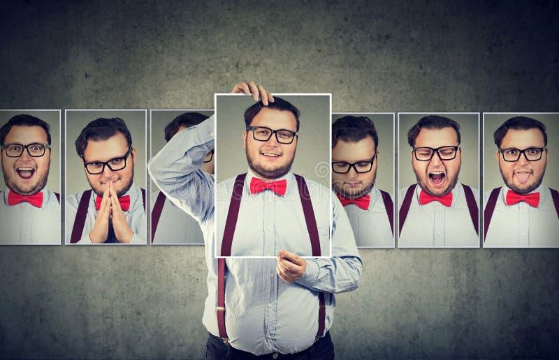 Uomo che ha oscillazioni di umore che posano alla macchina fotografica fotografia stock