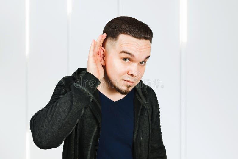 Uomo che ha problemi con l'udito, non è sordo Il tizio che gestiva origliare con la mano vicina all'orecchio, ascoltava gossip fotografie stock libere da diritti