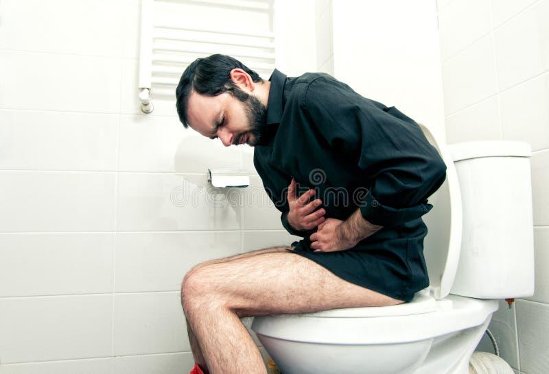 Uomo che ha problemi nella toilette immagini stock
