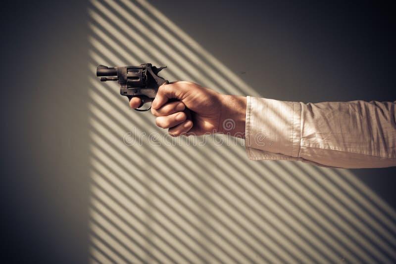 Uomo che indica revolver dalla finestra fotografia stock libera da diritti