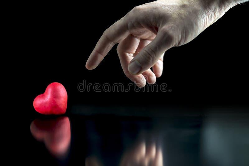 Uomo che indica un cuore rosso fotografia stock
