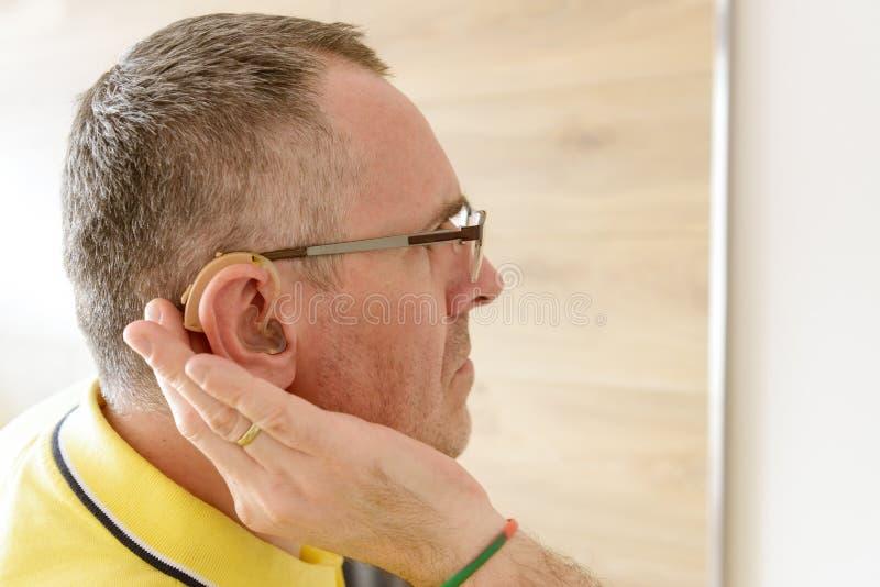 Uomo che indossa aiuto sordo fotografia stock libera da diritti