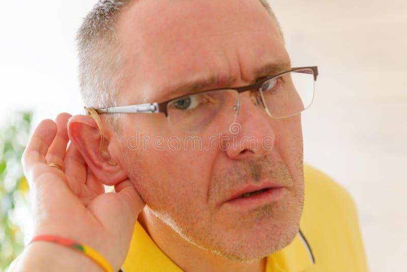 Uomo che indossa aiuto sordo immagine stock libera da diritti