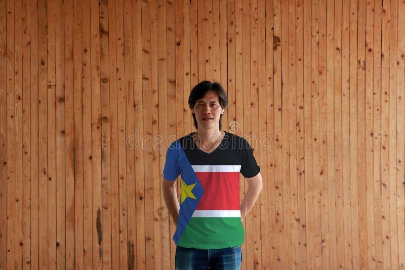 Uomo che indossa colore del sud della bandiera del Sudan della camicia e che sta con attraversato dietro le mani posteriori sui p fotografie stock