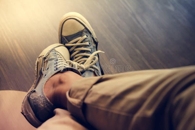 Uomo che indossa le vecchie scarpe da tennis blu in pantaloni marroni che si siedono sulla caffetteria, tono d'annata fotografia stock libera da diritti