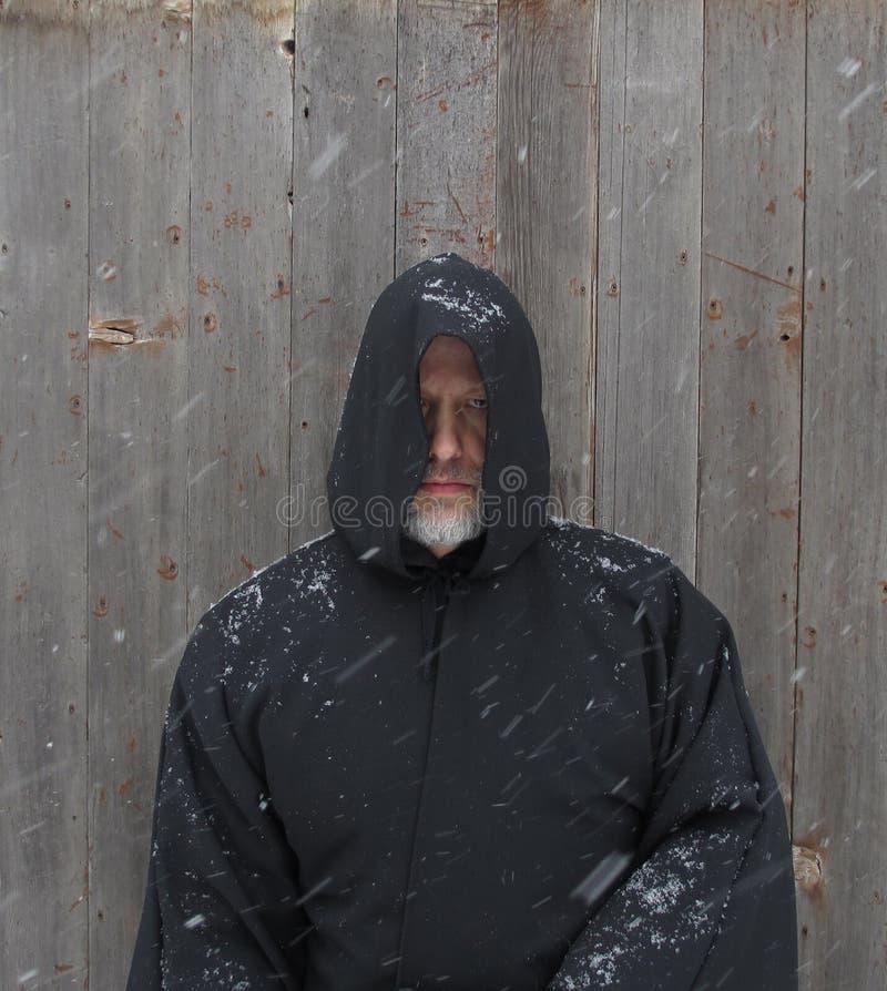 Uomo che indossa un capo incappucciato nero con neve che cade immagini stock