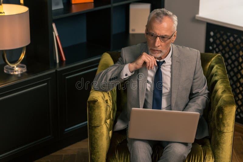 Uomo che indossa un vestito grigio e un legame blu scuro immagini stock libere da diritti