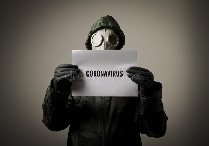 Uomo che indossa una maschera anti-gas in faccia e tiene in mano un foglio bianco con una nota sul CORONAVIRUS immagini stock libere da diritti