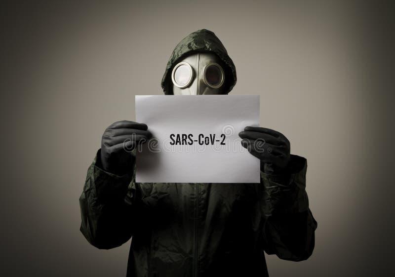 Uomo che indossa una maschera anti-gas in faccia e tiene in mano un foglio bianco con un testo sulla SARS-CoV-2 fotografia stock libera da diritti