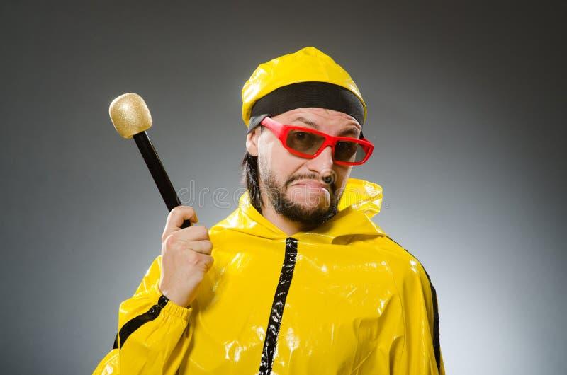 Uomo che indossa vestito giallo con il mic immagine stock