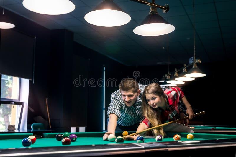 Uomo che insegna alla sua amica che gioca biliardo immagine stock libera da diritti