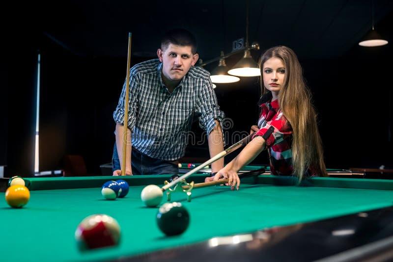 Uomo che insegna alla sua amica che gioca biliardo, coppia in pub fotografia stock