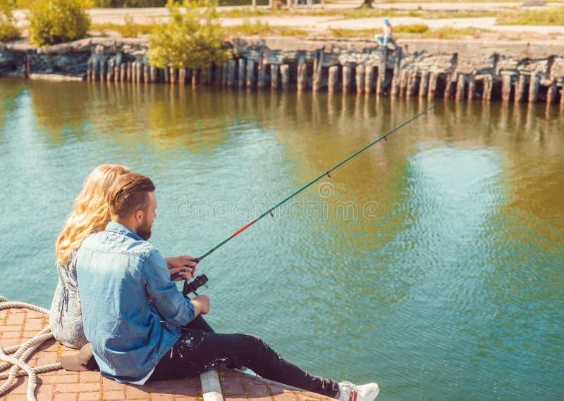 Uomo che insegna alla sua amica alla pesca Concetto della data, di amore e di hobby Priorit? bassa di autunno fotografia stock libera da diritti