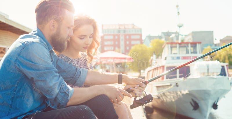 Uomo che insegna alla sua amica alla pesca Concetto della data, di amore e di hobby Priorit? bassa di autunno fotografia stock