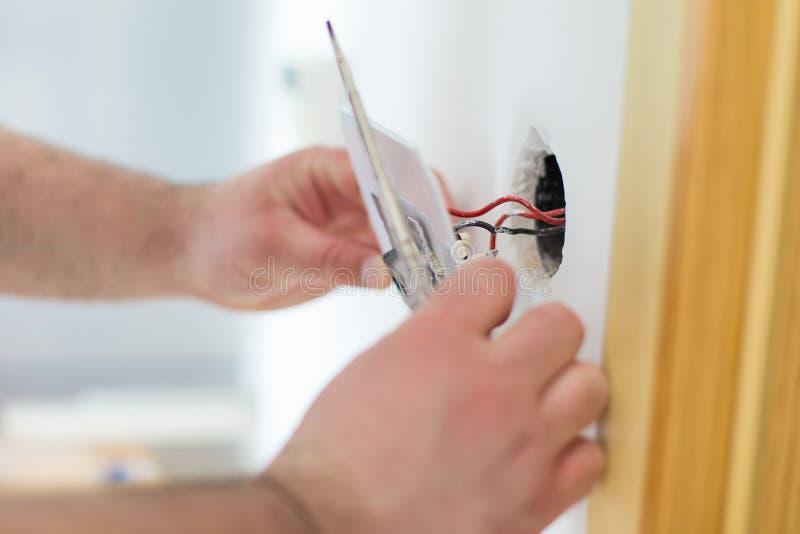 Uomo che installa interruttore della luce fotografia stock libera da diritti