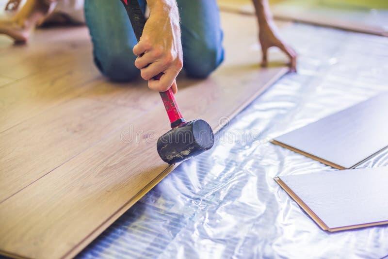 Uomo che installa nuova pavimentazione laminata di legno calore infrarosso del pavimento fotografie stock libere da diritti