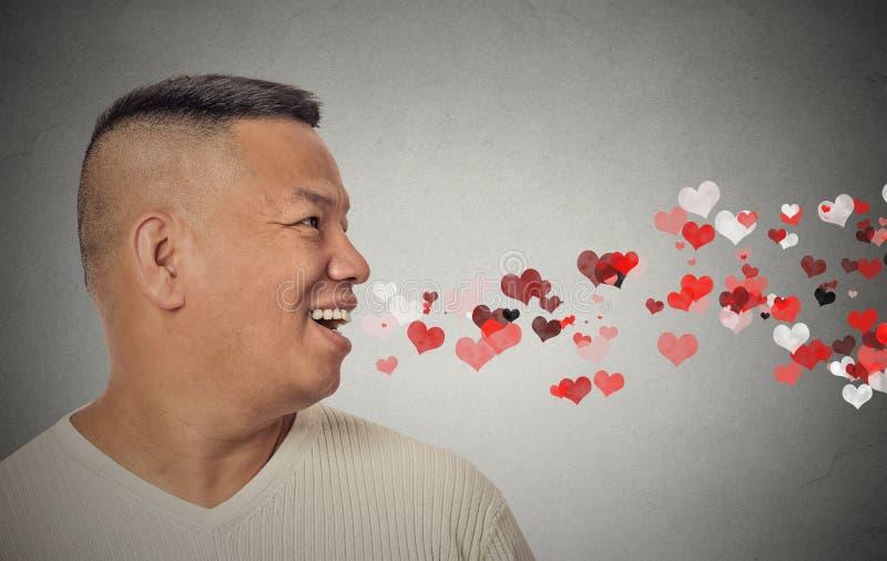 Uomo che invia i baci, cuori rossi che escono da bocca aperta fotografia stock
